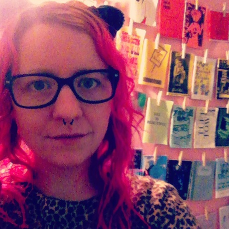 My silly face. In the background: A freshly-painted pink bedroom wall and a rainbow of zines.